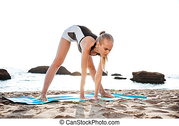 Peaceful young woman doing relaxing yoga exercises