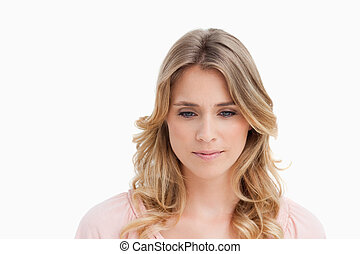 Peaceful young woman looking down against a white background