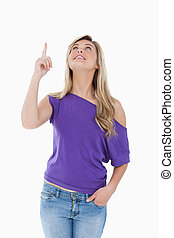 Peaceful young woman looking up while raising her finger