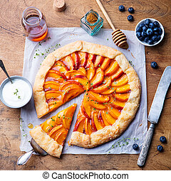Peach galette, pie, cake with honey and berry on a wooden background. Top view.