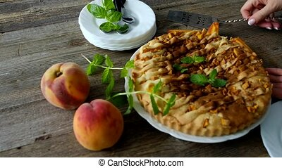 Peach homemade pie - Girl cutting a peach homemade pie on a...