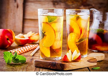 Peach ice tea in a glass with mint