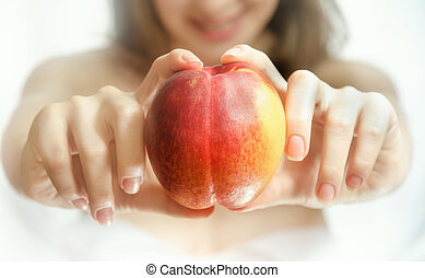 Peach in female hands. White background. Blurred image of...
