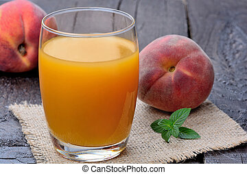 Peach juice in a glass on wooden table