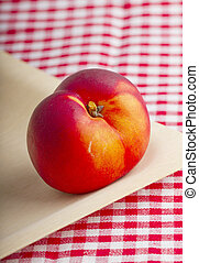 Peach - Single red peach over a wooden plate