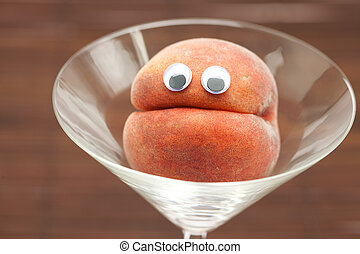 Peach with eyes in the glass martini on a bamboo mat