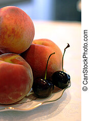 A plate of peaches and two cherries.