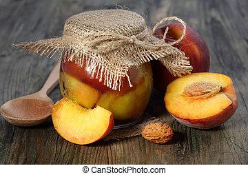 Peaches and pot of jam. - Peaches and pot of jam on a wooden...