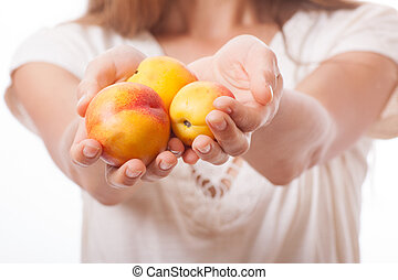 peaches in hand, isolated on white