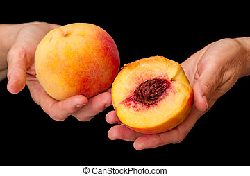 Peaches in hands on black - Peaches in hands isolated on...