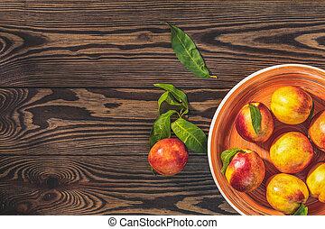 Peaches in orange plate on dark wooden background
