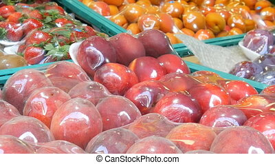 Peaches, Nectarine, apricots, strawberries, kiwi on street market counter under a special cellophane cloth, protected from dust and moisture.