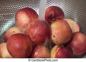 Peaches nectarine. Fresh red ripe nectarines washed under running water in a colander.