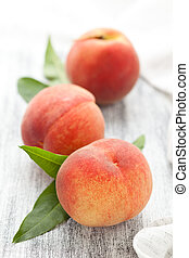 Peaches on rustic table. - Peaches with leaves on white ...