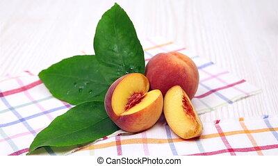 peaches, ripe peaches with a green leaf on a napkin - ripe...