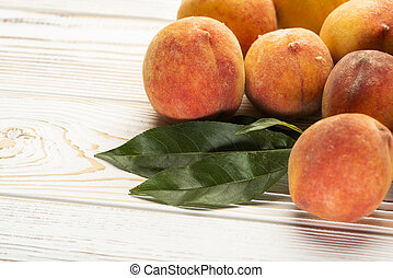 peaches with leaves close-up on the table