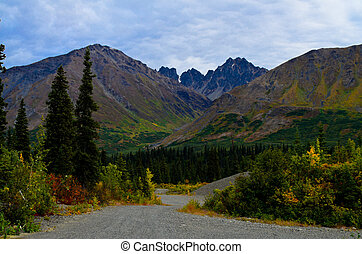 Magnificient view of a peak in the Alaska mountain range with fall foliage and evergreens with the road in the center
