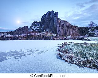 Peak of basalt pillars covered by snow, frozen pool. Full moon in blue sky in the background.