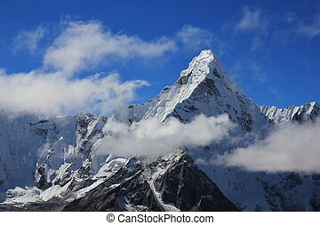 Peak of Mt Ama Dablam surrounded by clouds