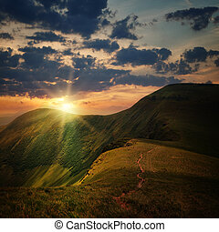peak of the hill with pathway and mountain sunset rays on ...