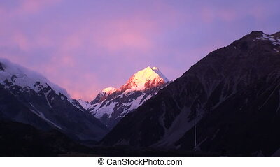 Peaks and ridges of snow mountain on sunset panorama in New Zealand.