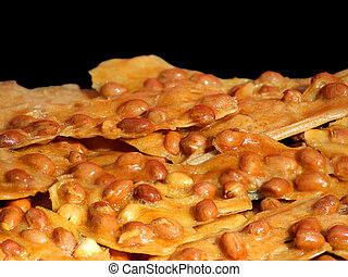 Peanut Brittle - Close view of peanut brittle against black...