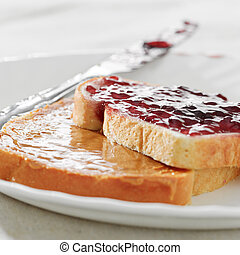 Peanut butter and jelly on pieces of bread.