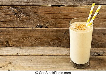 Peanut butter banana oat breakfast smoothie with paper straws against a rustic wood background