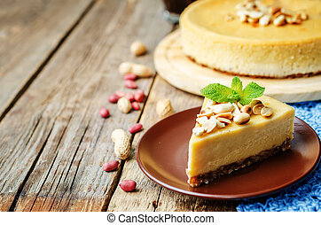 peanut butter cheesecake on a dark wood background. toning. ...