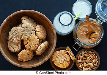 Peanut butter cookies with milk on a black background