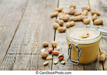 peanut butter on a dark wood background. tinting. selective focus