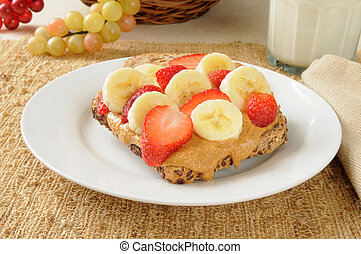 Peanut butter sandwich with banana and strawberries