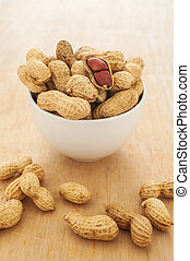 Peanut in a white bowl on wooden background