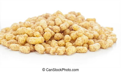 Peanut puffs rotating on the white table with white seamless...