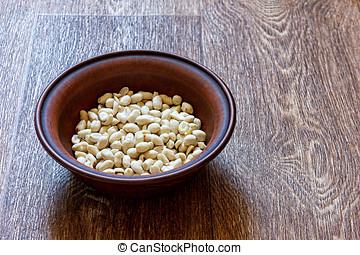 Peanuts in a plate on  wooden table