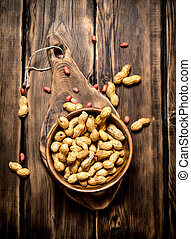 Peanuts in a wooden bowl .