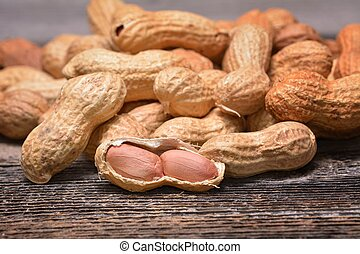 Peanuts in shells on wooden background