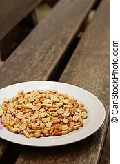 Peanuts in white plate on a wood background