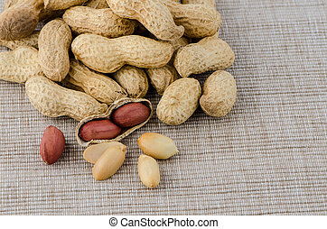 Peanuts on old raffia background.