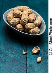 Peanuts on petrol-colored wood in bowl