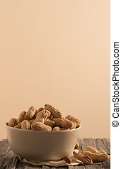 Peanuts with shell in a white bowl