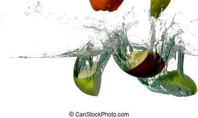 Pear and apple segments plunging into water on white...