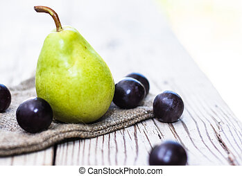 Pear and grapes on wooden table.