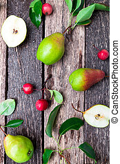 Pear and small apple on wooden rustic background.