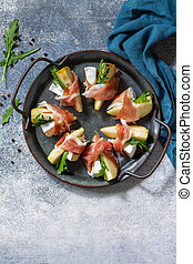 Pear appetizer with jamon, arugula and brie cheese on a light stone table. Top view flat lay background. Copy space.