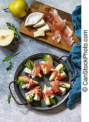Pear appetizer with jamon, arugula and brie cheese on a light stone table. Top view flat lay background.