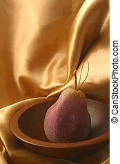 Pear Ornament - A pear ornament in a wooden bowl on gold...