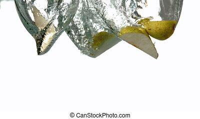 Pear segments plunging into water on white background in...
