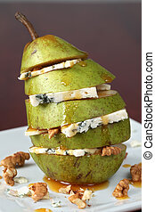 Pear with Gorgonzola, walnuts and honey on a plate