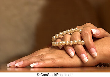 Pearl and hand - Hand with a pearl necklace touching.